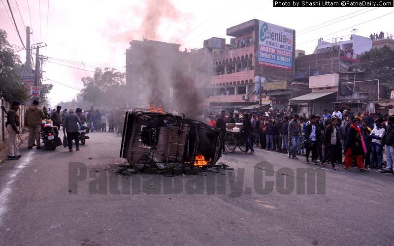 An auto-rickshaw burns after an angry mob torches it following a deadly accident.