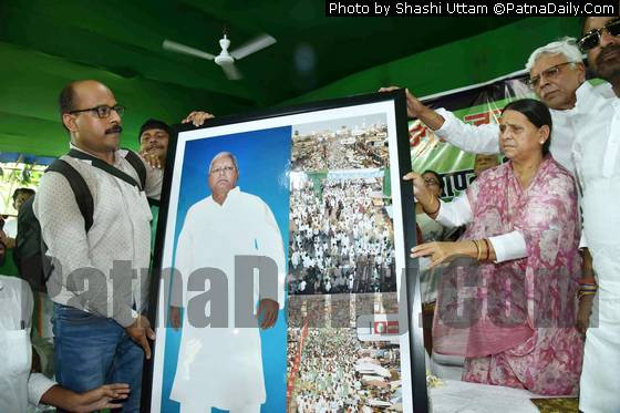 RJD leader Rabri Devi showing a poster of her husband Lalu Prasad Yadav at the foundation day of the party on Friday.