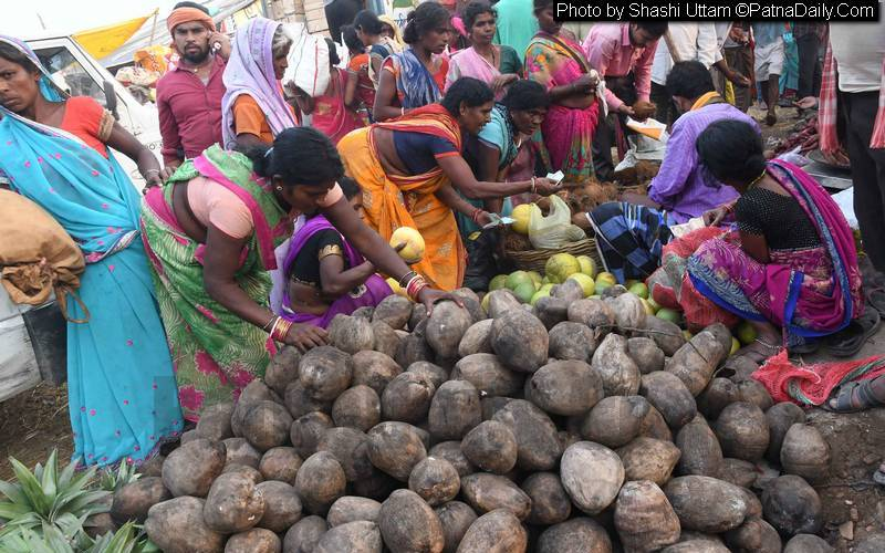 Women buying coconuts a day before the commencement of Chhath festival.
