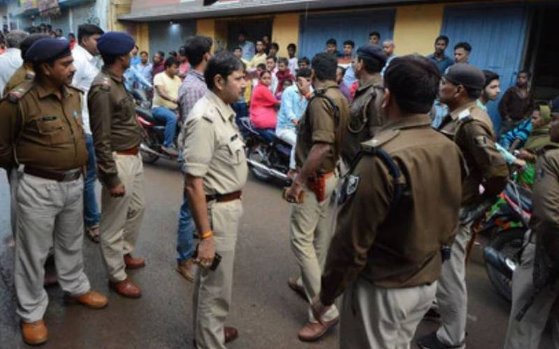 Police gather at the crime scene in Patna City on Friday night.