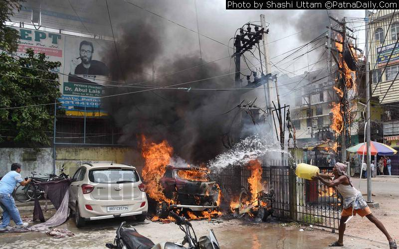 People try to douse flame in a fire caused by electrical short-circuit in Patna on Tuesday.